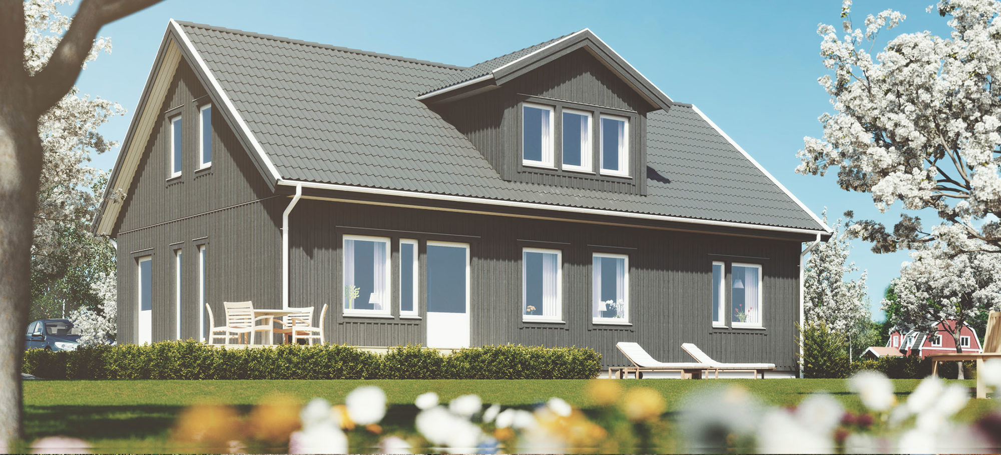 1,5-planshus. Grå fasad och grått tak. Vacker takkupa på baksidan.