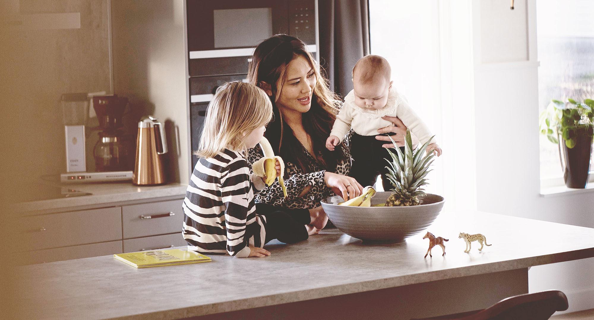 Sol 170 kök med köksö. En mamma leker med sina två barn.